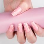 corso-decorazione-unghie-gioia-del-zotto-ha-eseguito-un-decoro-armonioso-in-bianco-con-tratti-sottili-sul-monocolore-rosa-dando-luce-con-glitter-dorato