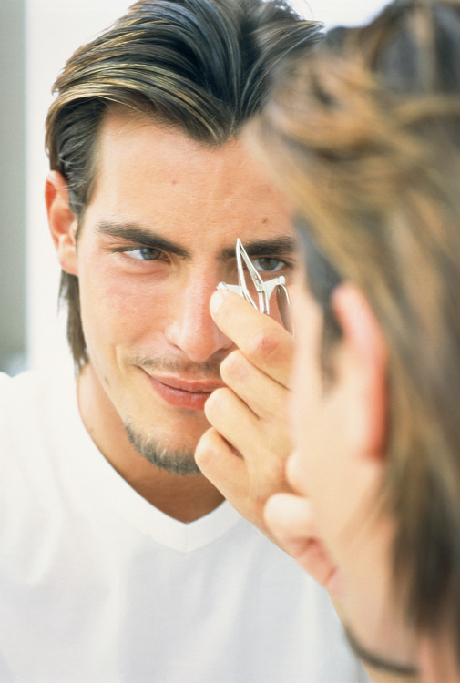 Young man plucking his eyebrows in front of mirror --- Image by © Klawitter Productions/Corbis